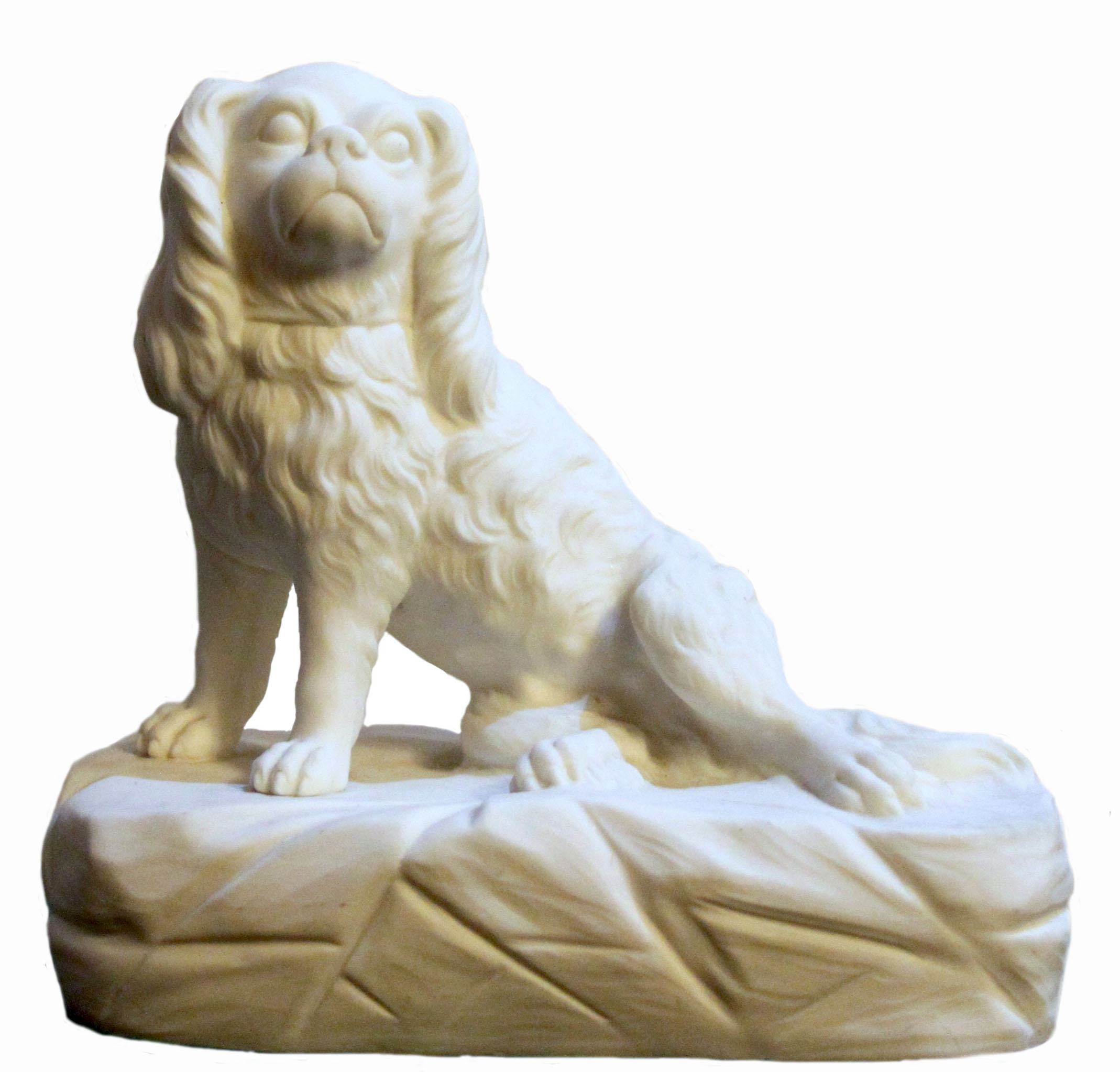 Click to see full size: A Parian / biscuit ware model of  a recumbent King Charles Cavalier Spaniel seated on a cushion.