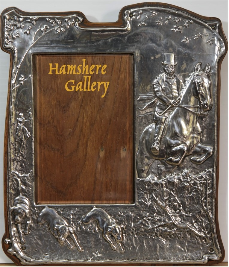 Click to see full size: An early 20th Century easel back silver photograph frame depicting huntsman and running hounds