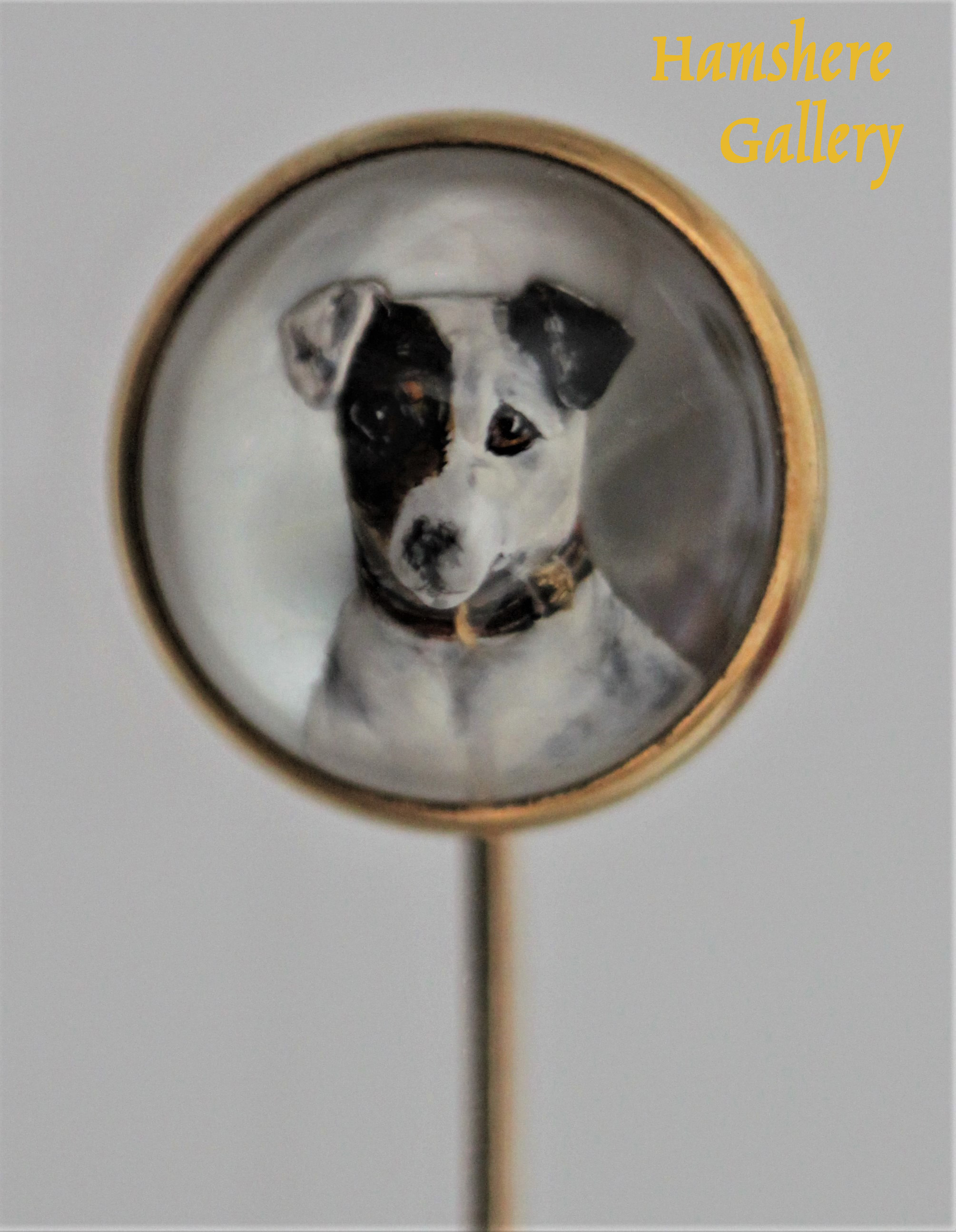 Click to see full size: An 18 carat gold reverse intaglio crystal stick pin of a Smooth-haired Fox Terrier / Jack Russell set by Tiffany